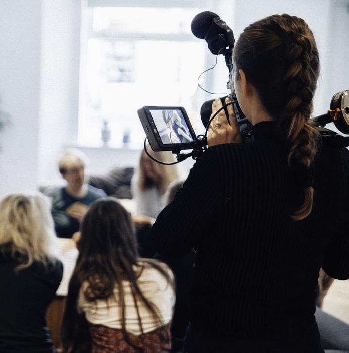 photo d'une caméraman qui film une conférence